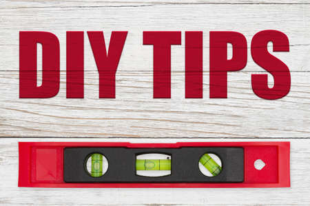 DIY Tips word message with red and black level on distressed whitewash Stock Photo