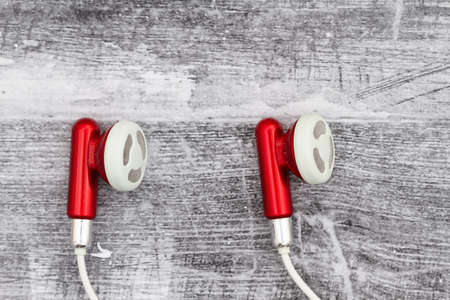 Earbuds red and white for phone on black grunge wood