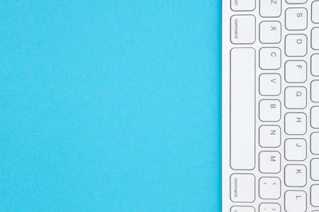 Gray keyboard on a blue background with copy space for your tech message