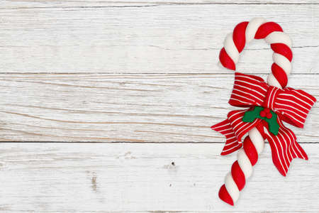 Christmas background with retro Christmas candy cane on distressed whitewash with copy space for Christmas or holiday message