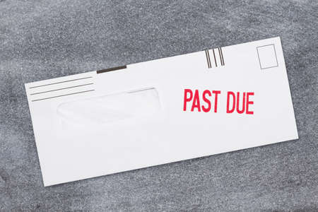 Past Due word message on business envelope on a weathered gray stone