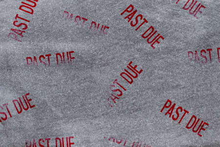 Past Due word message stamp on a weathered and distressed gray stone