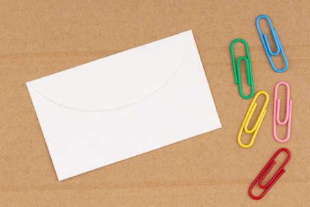 Blank envelope on brown textured cardboard with paperclips background with copy space for message