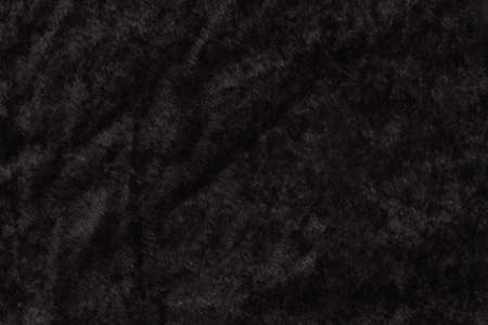 Black velvet textured fabric material background with copy space for message or use as a texture