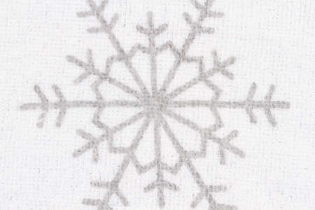 Snowflake on white textured fabric closeup background with copy space for message
