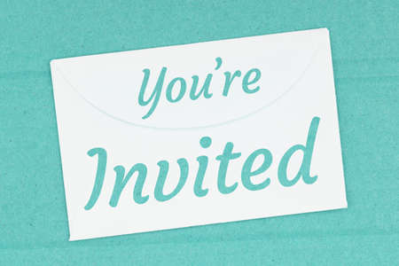You're Invited word message on white envelope on teal textured cardboard