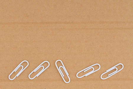 Brown textured cardboard with paperclips closeup background with copy space for message or use as a texture