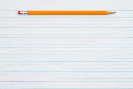 Retro lined school paper with a pencil background with copy space for your school message 免版税图像