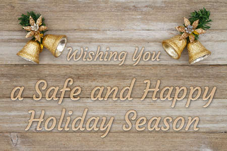 Season's Greeting message with gold Christmas bells with grunge wood