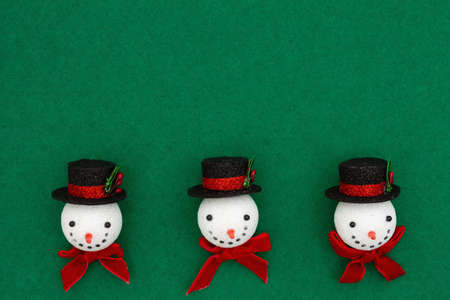 Christmas snowmen with top hats on green felt background with copy space for your holiday message