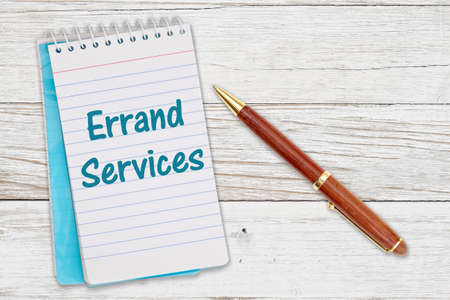 Errand Services message on retro lined paper notepad on a weathered wood desk with a pen
