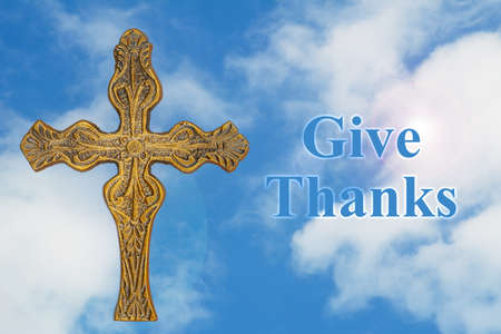 Give Thanks message with a vintage weathered bronze metal decorative detailed cross with clear blue sky
