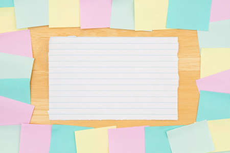 Sticky note background with multi-color notes and note paper on a wood desk wood with copy space for your office or reminder message