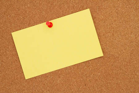 Retro yellow paper index card with pushpin on corkboard with copy space for your message