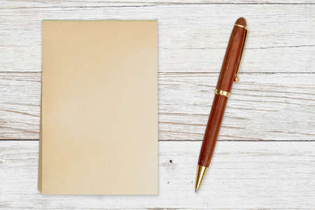 Blank retro old yellowed paper notepad with a pen on weathered wood