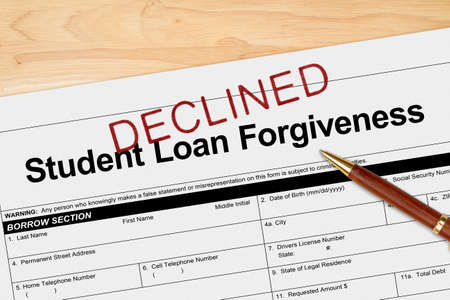 Student Loan Forgiveness application declined with pen on a wood desk Imagens