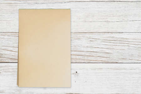 Blank retro old yellowed paper notepad on weathered wood