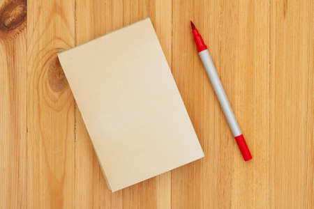 Blank retro old yellowed paper notepad with red marker on wood desk