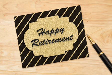 Happy Retirement message on a black and gold greeting card on wood desk