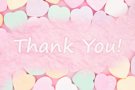 Thank you pink greeting card over candy hearts