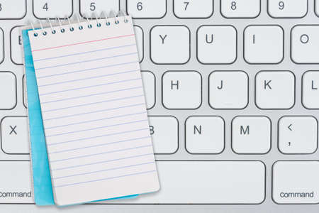 Blank blue notepad on gray keyboard with copy space for your tech of business message 版權商用圖片