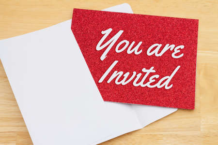 You are invited red glitter greeting card with an envelope on a desk 版權商用圖片