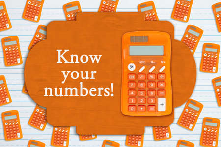 Know your numbers sign on orange calculator on ruled paper 版權商用圖片
