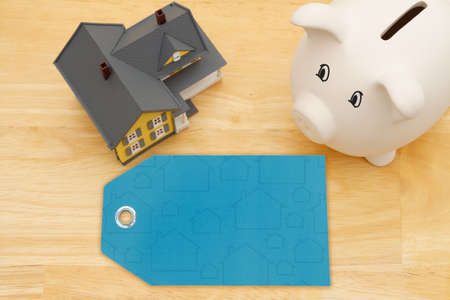 Blank gift tag with a model house with a piggy bank on wood desk for your buying or selling real estate message