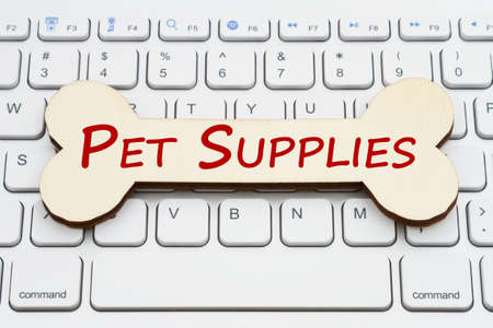 Pet supplies message on wood dog bone on gray keyboard with copy space for your online pets message