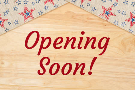 Opening soon wood sign with blue and red stars ribbon 版權商用圖片