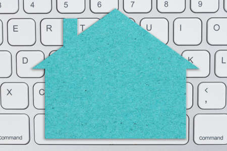 Blank teal house sign on gray keyboard for your online sales message