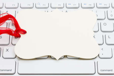 Blank gift tag with red ribbon on gray keyboard with copy space for your online sales message