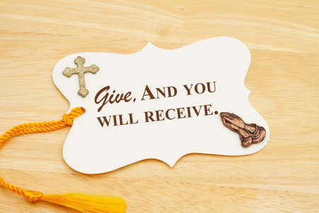 Give and you will receive message gift tag with yellow ribbon praying hands and cross on wood desk