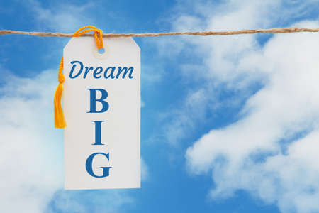 Dream Big message white gift tag with yellow ribbon over sky 版權商用圖片