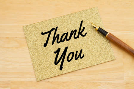 Thank you gold glitter greeting card with a pen on a desk