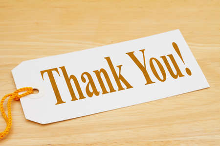 Thank you message on a gift tag with yellow ribbon on wood desk