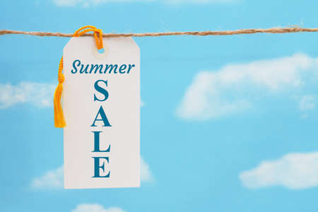 Summer Sale message white gift tag with yellow ribbon over sky