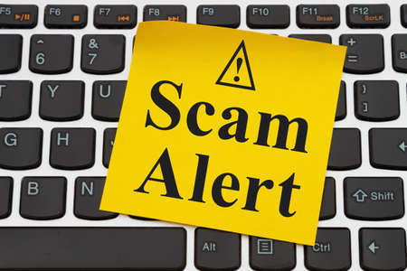 Scam Alert media message on yellow sticky note on a black and silver keyboard 版權商用圖片