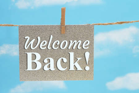 Welcome Back gray greeting card over hanging clear blue sky