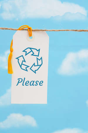 Recycle Please message white gift tag with yellow ribbon over sky