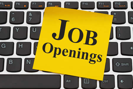 Job Openings media message on yellow sticky note on a black and silver keyboard 版權商用圖片