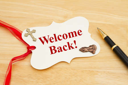 Welcome Back message gift tag with red ribbon praying hands, cross and pen on wood desk 版權商用圖片