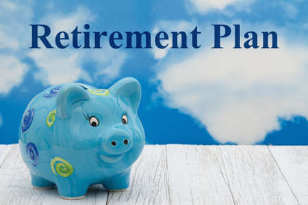 Retirement Plan message with a piggy bank on weathered wood with clear sky