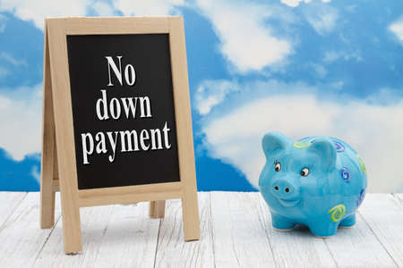 No down payment message standing chalkboard with a piggy bank on weathered wood with clear sky