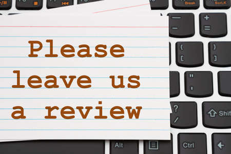 Please leave us a review message white index card on a black and silver keyboard