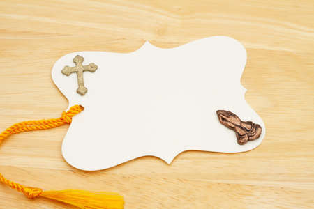 Blank gift tag with yellow ribbon praying hands and cross on wood desk 版權商用圖片
