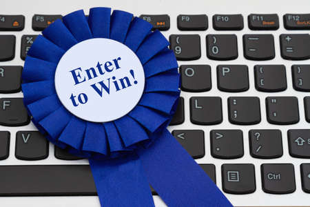 Enter to win message on a blue prize ribbon on keyboard for your online giveaways