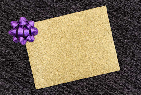 Blank gold glitter greeting card with purple bow on black background