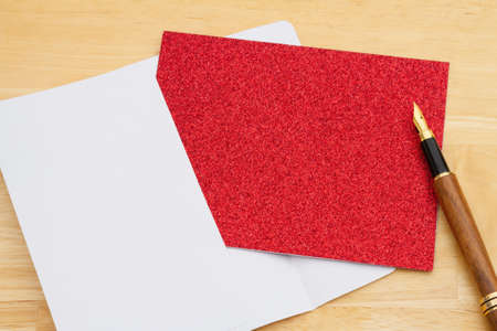 Blank red glitter greeting card with a pen and an envelope on a desk 版權商用圖片