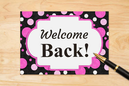 Welcome Back message on a black and pink polka dots greeting card on wood desk 版權商用圖片